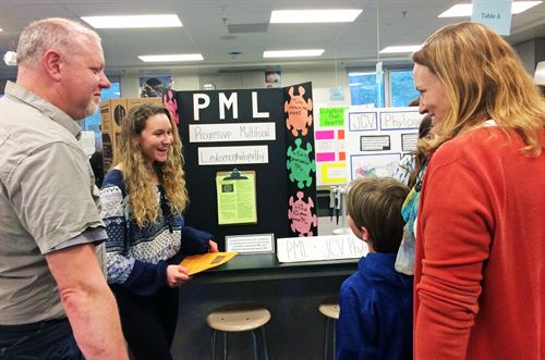 Student presenting project to a family at Open House.