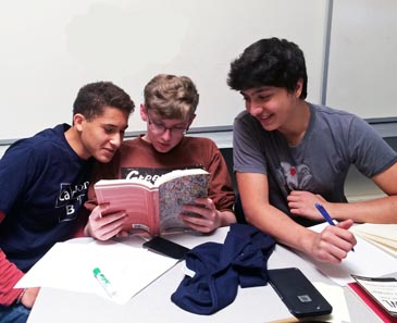 Students reading a book of poetry.