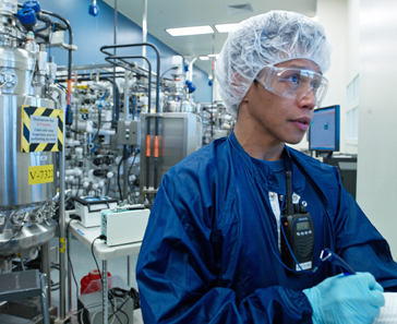 Genentech employee with lab coat, gloves, and goggles